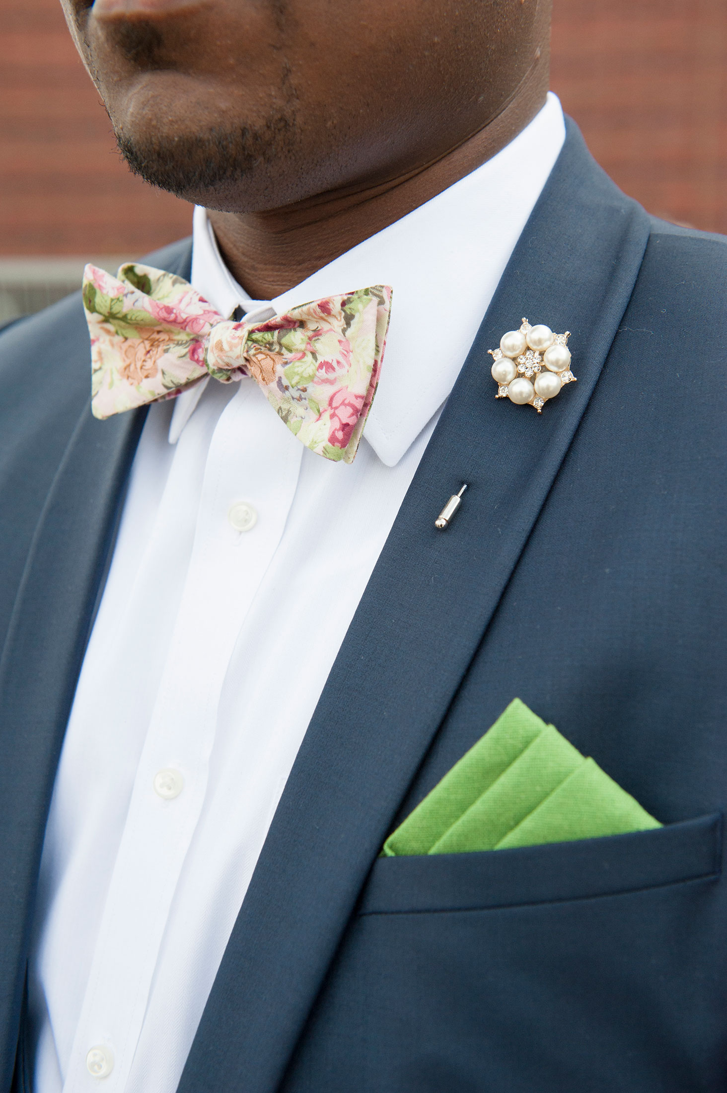 SEG_Man wearing floral bow tie and jewel pin Boutonniere