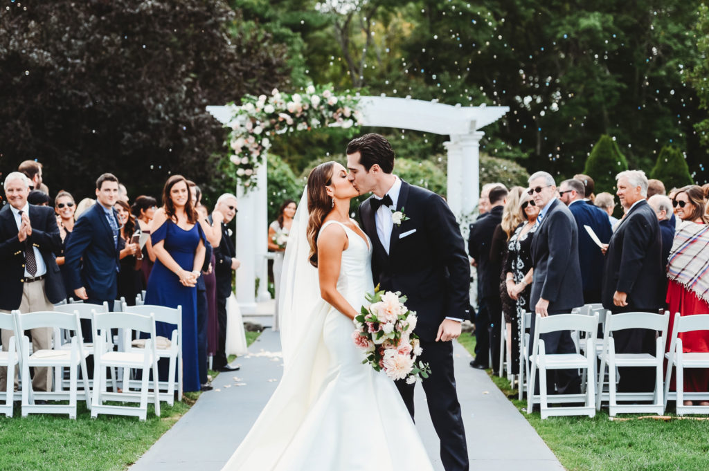 bride and groom kissing after walking down aisle
