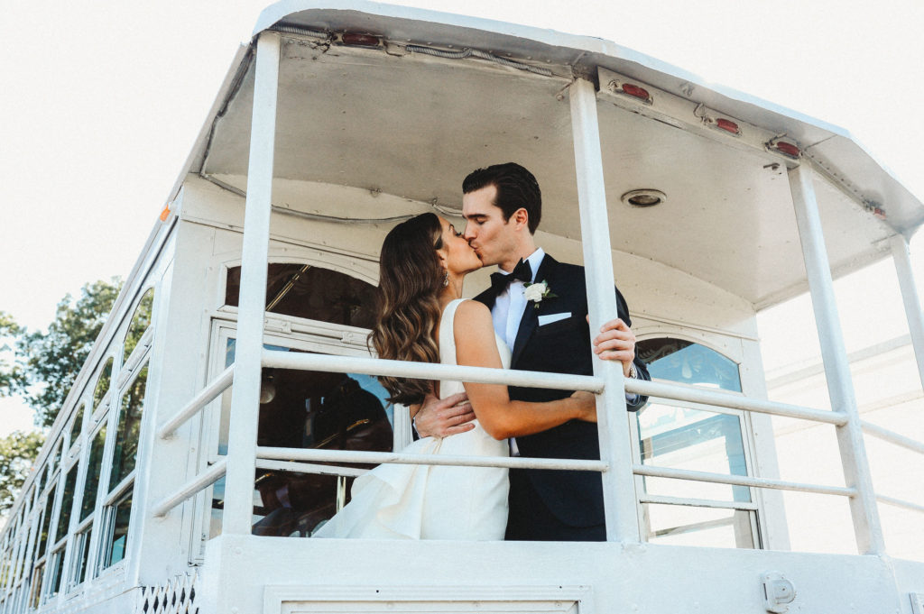 bride and groom kissing on trolley