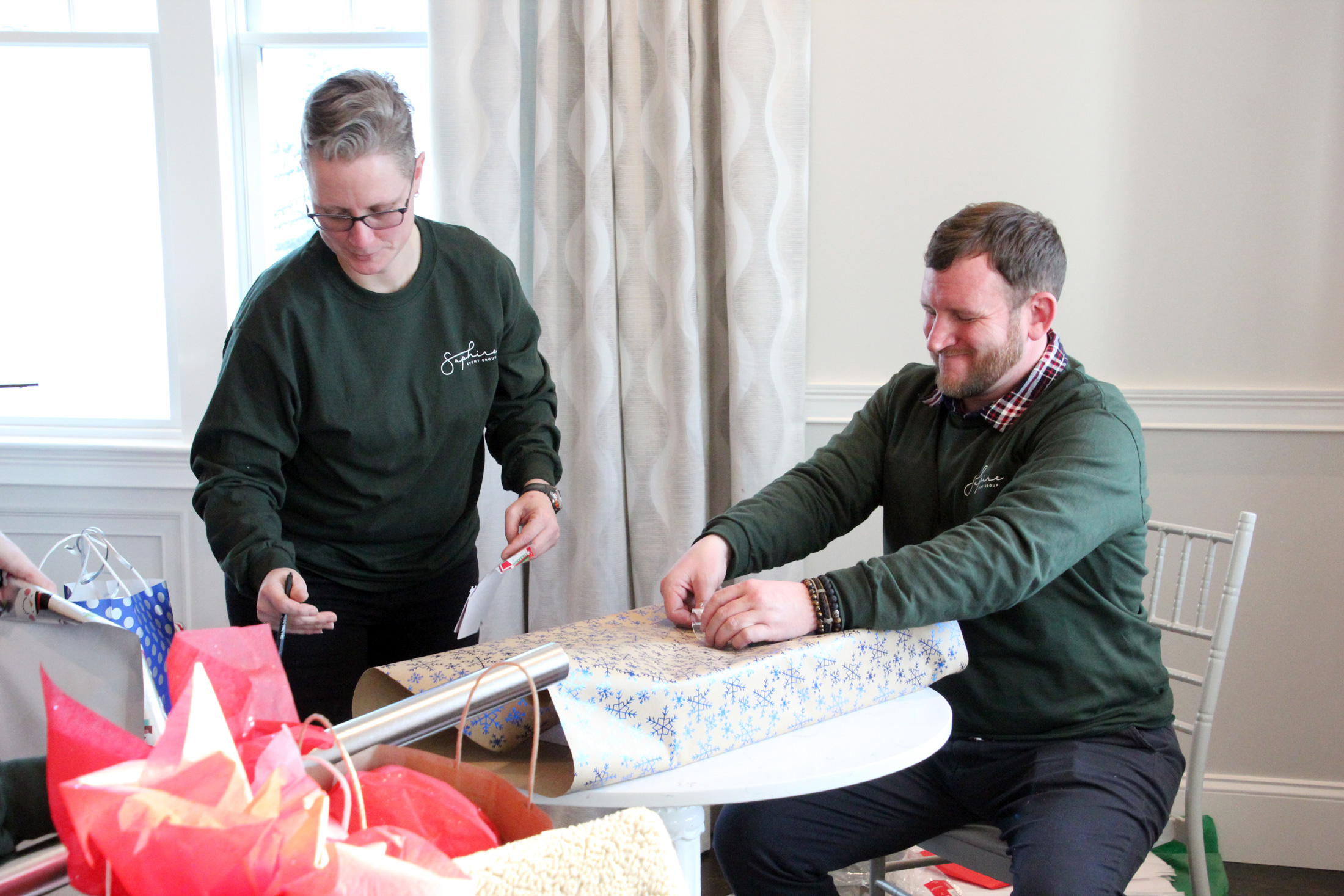 SEG employees work together to wrap holiday gifts