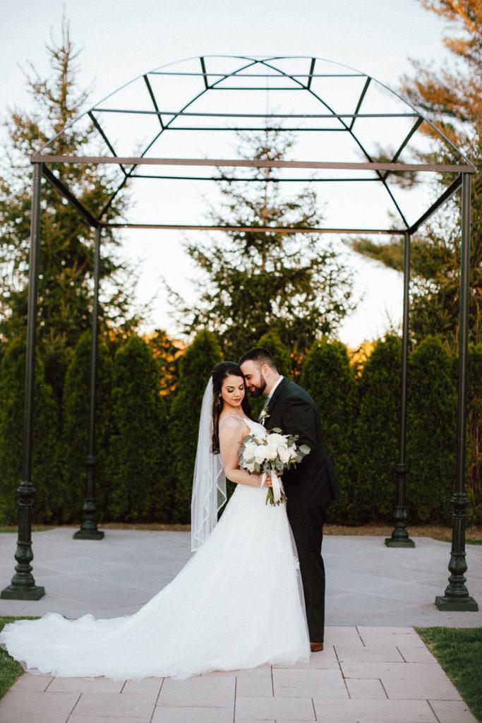 bride and groom under pergola