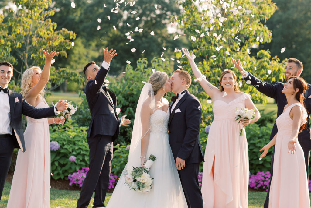 bride and groom kissing while wedding party throws flower petals
