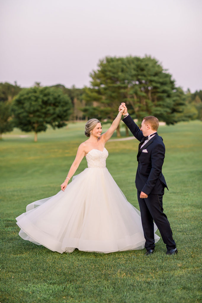 groom spinning bride on green