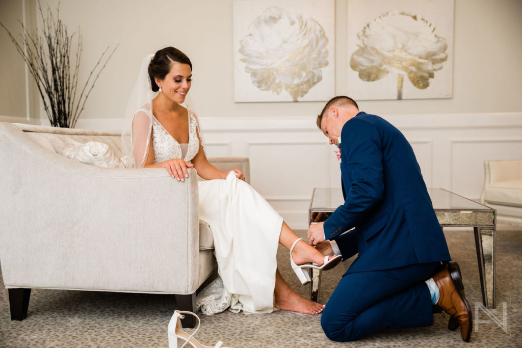 groom helping bride with show in bridal suite