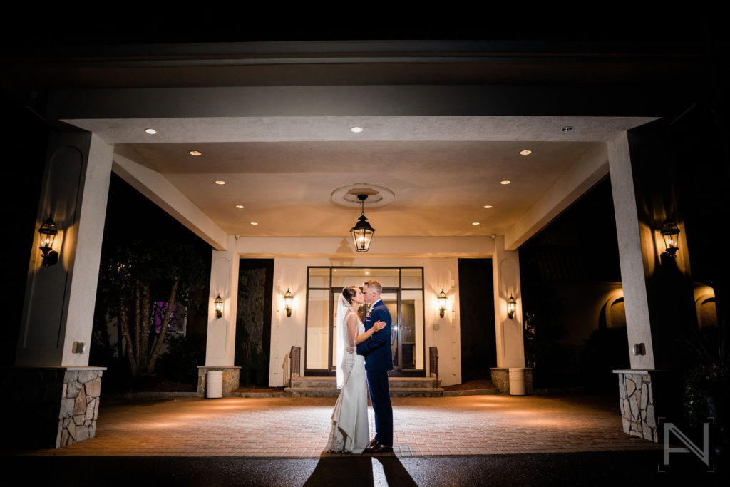 bride and groom kissing in front of entrance
