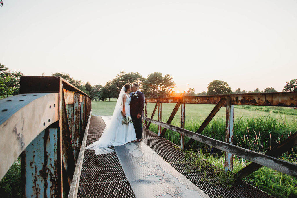 bride and groom on the bridge during sunset