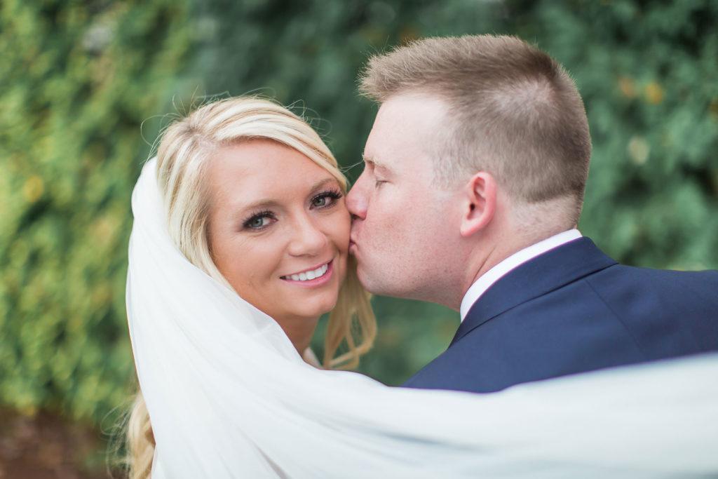 groom kissing bride's cheek