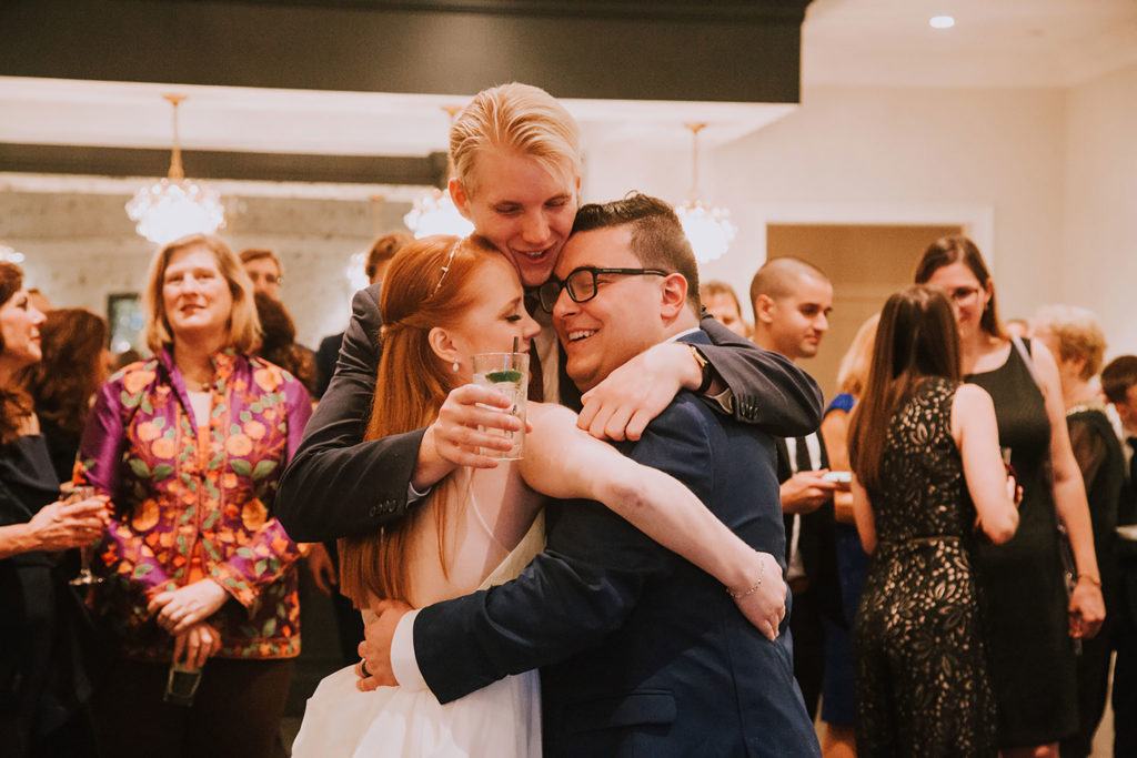 bride and groom hugging guest at cocktail hour