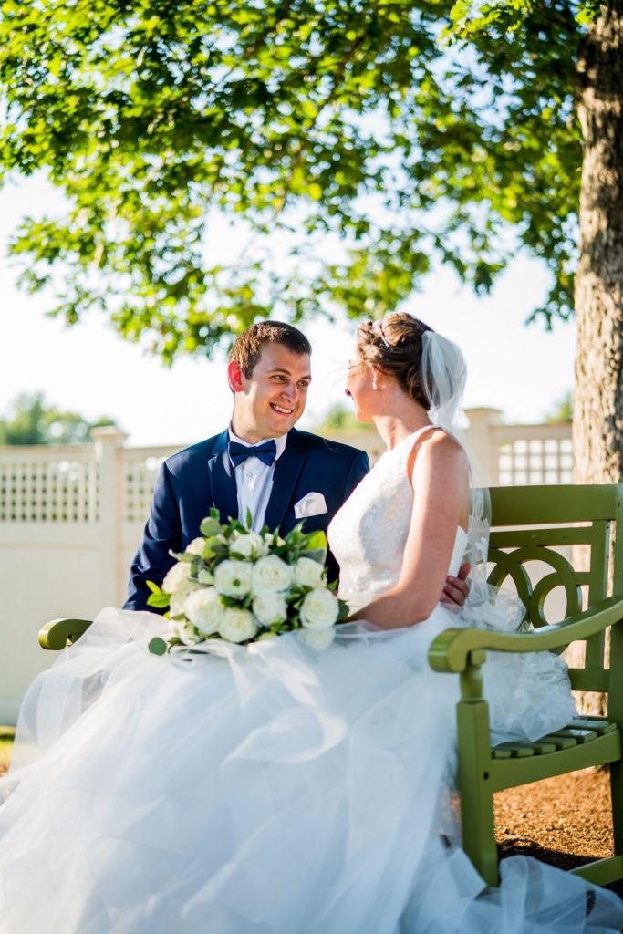 bride and groom sitting on garden bench