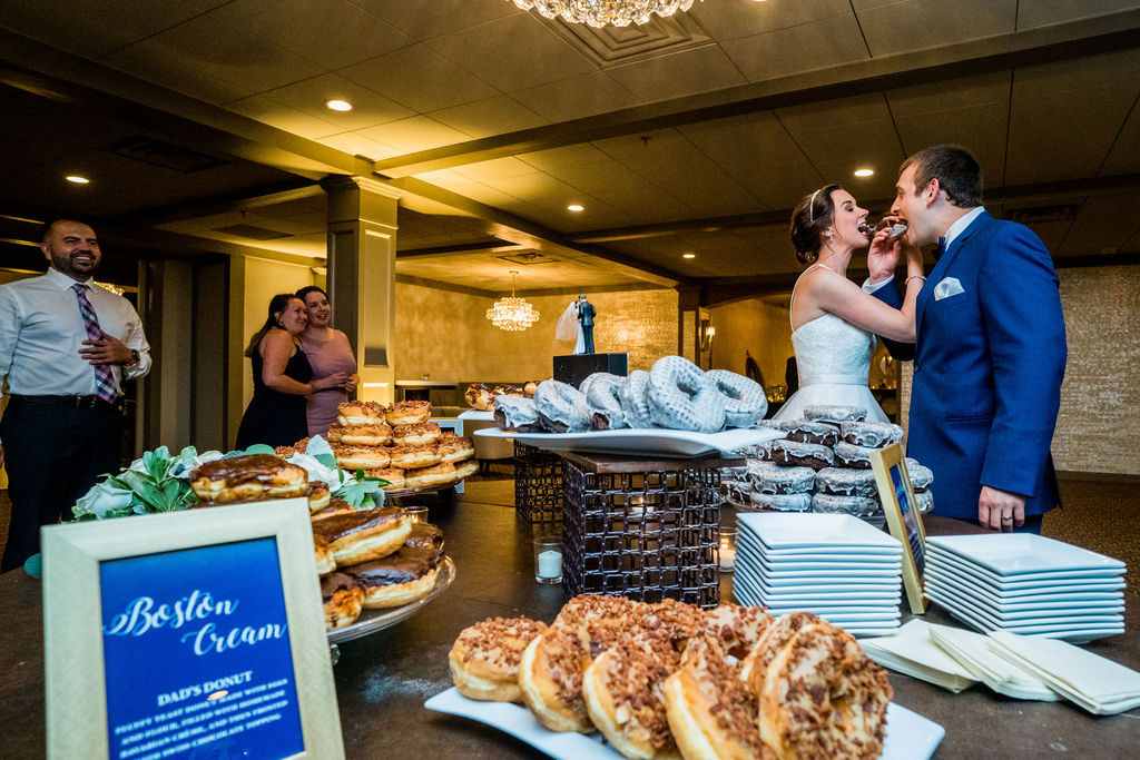 bride and groom kissing at donut table