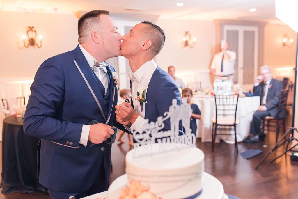 The Villa Madera August wedding Chris and Jason kissing during cake cutting