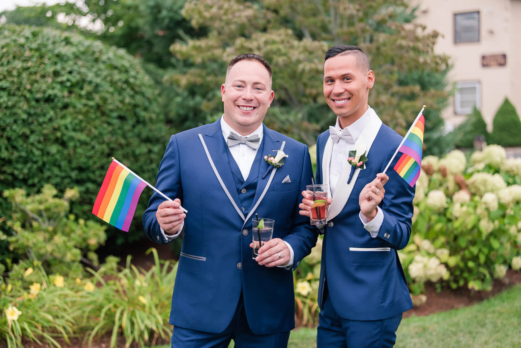 The Villa Madera August wedding Chris and Jason holding pride flags