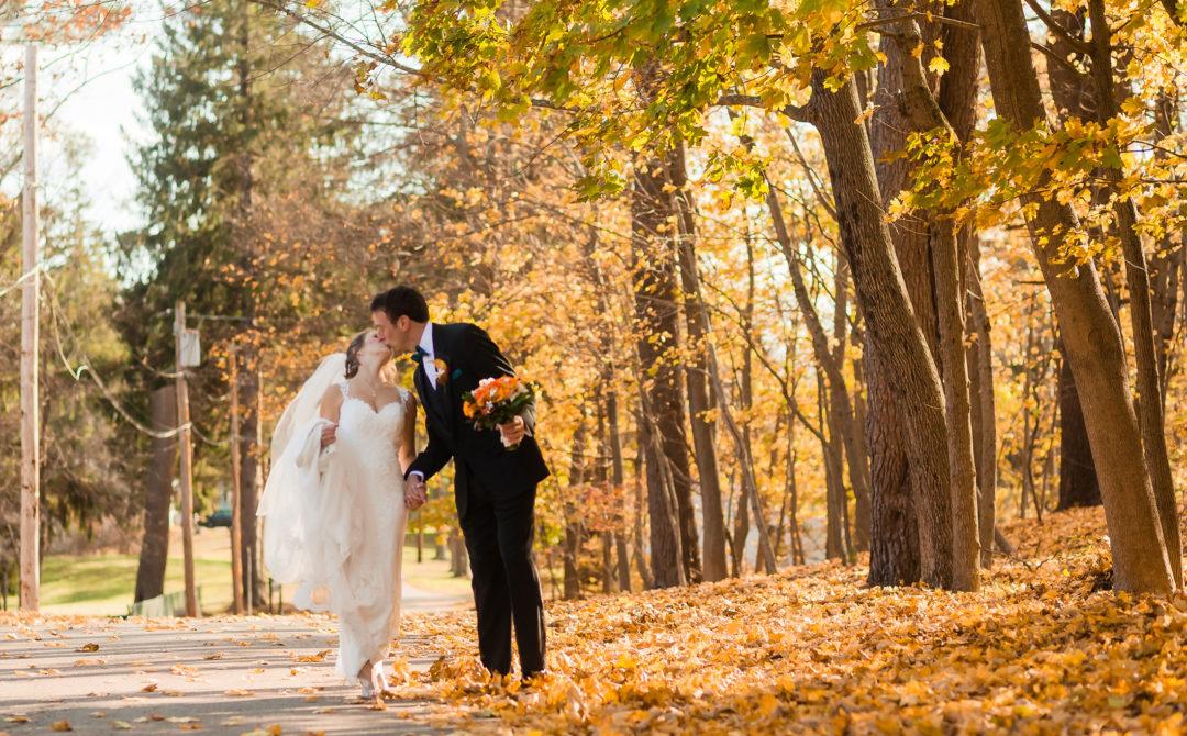 bride and groom kissing fall