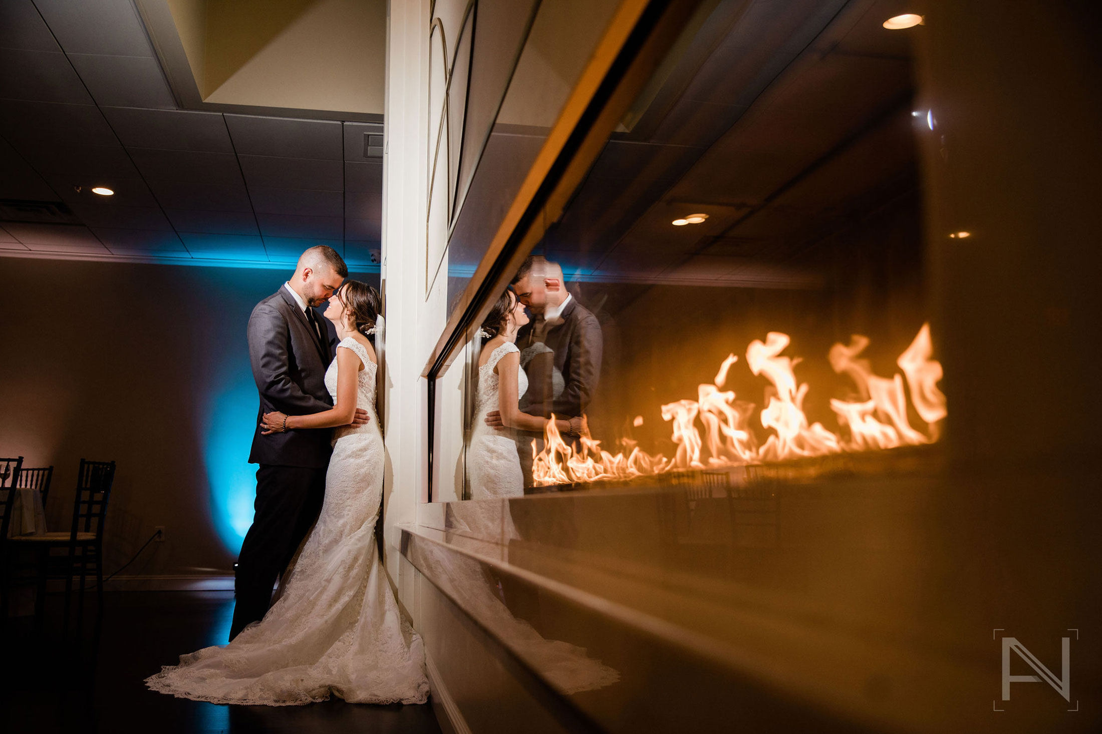 couple next to fireplace in ballroom